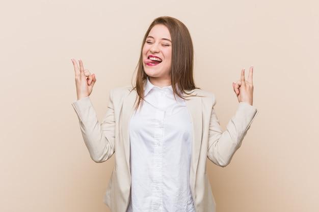 Femme d'affaires jeune montrant le geste de la roche avec les doigts