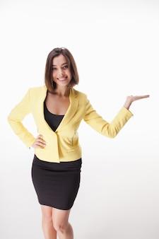 Femme d'affaires jeune montrant quelque chose posant
