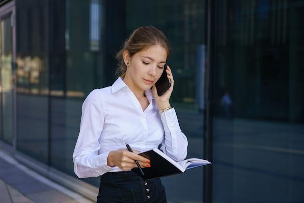 Femme d'affaires jeune parler au téléphone et écrire dans un cahier. dans une chemise blanche debout dans l'immeuble de bureaux