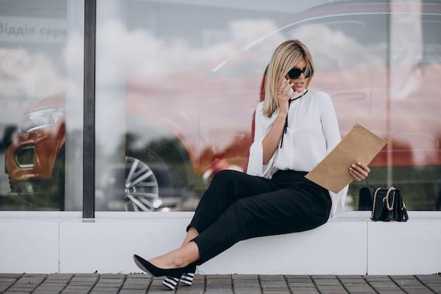 Femme d'affaires jeune parler au téléphone et lire des documents