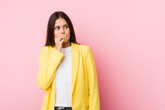 Femme d'affaires jeune réfléchie à la recherche d'un espace de copie couvrant la bouche avec la main.