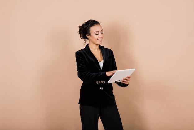 Femme d'affaires jeune réussie avec les mains jointes en souriant sur fond gris en studio