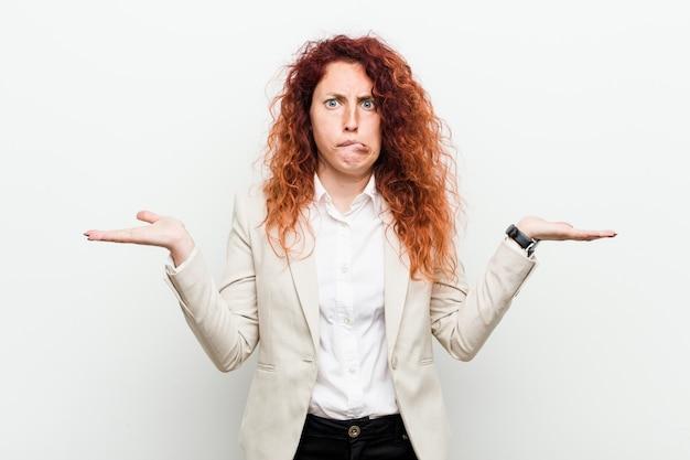 Femme d'affaires jeune rousse naturelle isolée contre blanc haussant les épaules, douteux et confus, pour tenir une copie.