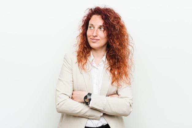Femme d'affaires jeune rousse naturelle isolée contre un mur blanc souriant confiant avec les bras croisés.