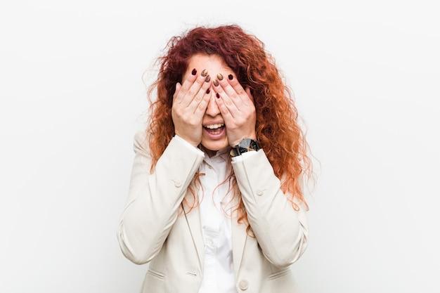 Femme d'affaires jeune rousse naturelle isolée contre les yeux blancs couvre les mains avec les mains, un large sourire attend une surprise.
