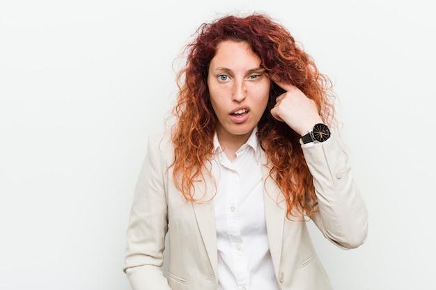 Femme d'affaires jeune rousse naturelle isolée sur fond blanc montrant un geste de déception avec l'index.