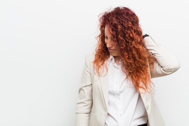 Femme d'affaires jeune rousse naturelle isolée sur fond blanc souffrant de douleurs au cou due à un style de vie sédentaire.