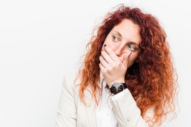 Femme d'affaires jeune rousse naturelle réfléchie à la recherche d'un fond couvrant la bouche avec la main.