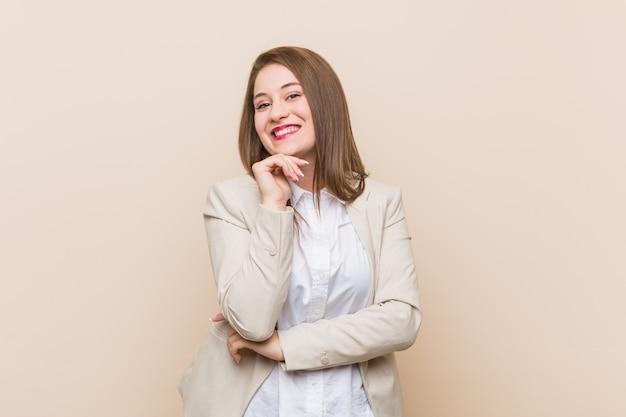 Femme d'affaires jeune souriant heureux et confiant, touchant le menton avec la main.