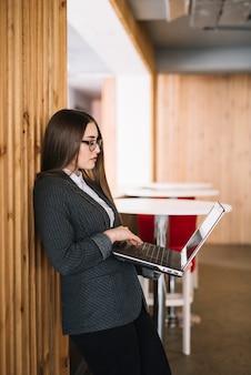 Femme d'affaires jeune tapant sur un clavier d'ordinateur portable au mur