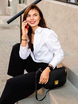 Femme d'affaires jeune avec téléphone portable assis près du restaurant et souriant.