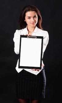 Femme d'affaires jeune tenant presse-papiers sur fond noir