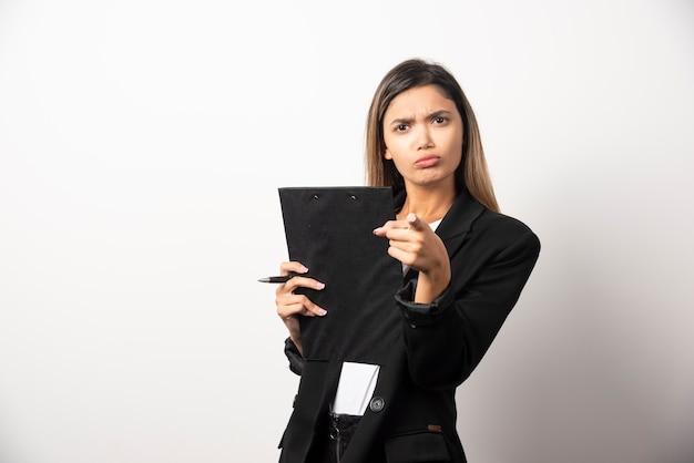 Femme d'affaires jeune tenant le presse-papiers et pointant vers la caméra.