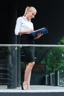 Femme d'affaires joyeuse debout avec des dossiers sur le balcon en verre à l'extérieur