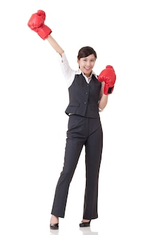 Femme d'affaires joyeuse lever les mains avec des gants de boxe rouges, portrait de pleine longueur isolé un fond blanc.