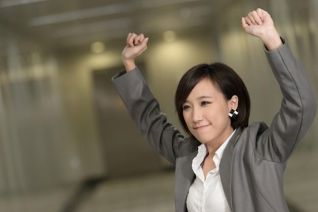 Femme d'affaires joyeuse et passionnante d'asie à l'intérieur de bâtiments modernes.