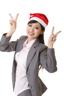 Femme d'affaires joyeuse portant un chapeau de noël, portrait agrandi sur fond blanc.