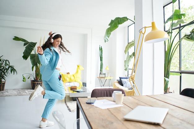 Une femme d'affaires latina réussie danse en tenue de bureau célébrant joyeusement au travail