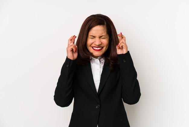 Femme d'affaires latine d'âge moyen isolé des doigts croisés pour avoir de la chance