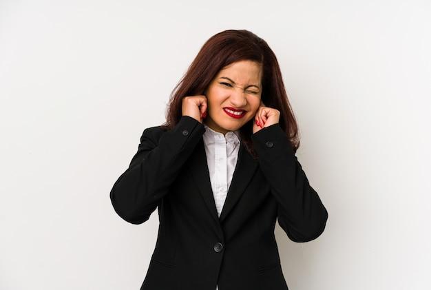 Femme d'affaires latine d'âge moyen isolée couvrant les oreilles avec les mains.