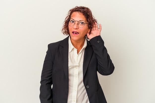 Femme d'affaires latine d'âge moyen isolée sur fond blanc essayant d'écouter un potin.