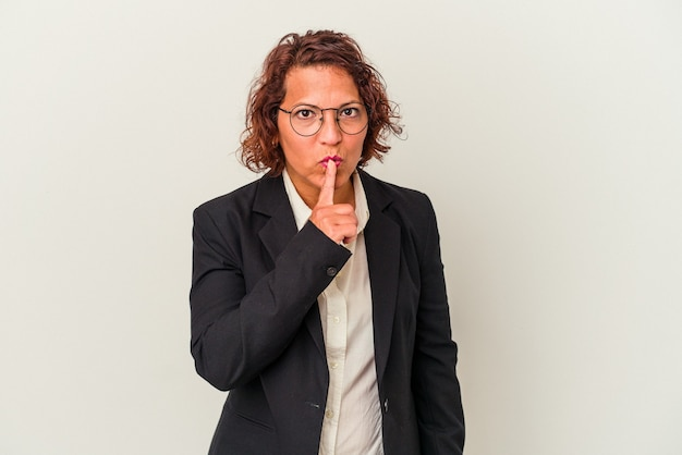 Femme d'affaires latine d'âge moyen isolée sur fond blanc gardant un secret ou demandant le silence.