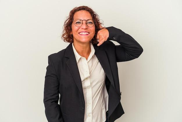 Femme d'affaires latine d'âge moyen isolée sur fond blanc montrant un geste d'appel de téléphone portable avec les doigts.