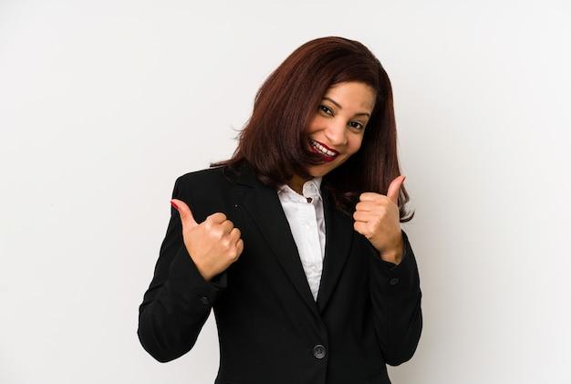 Femme d'affaires latine d'âge moyen isolée soulevant les deux pouces vers le haut, souriant et confiant.