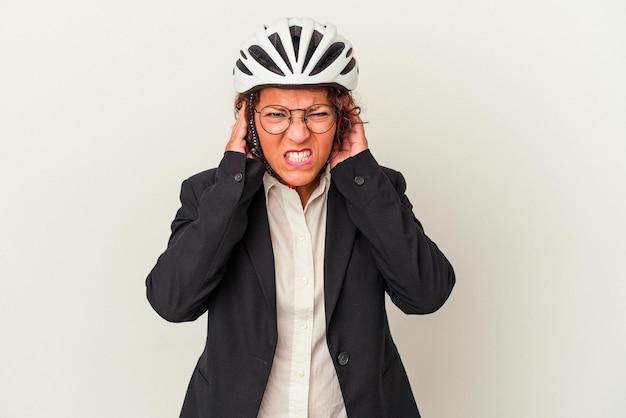 Femme d'affaires latine d'âge moyen portant un casque de vélo isolé sur fond blanc couvrant les oreilles avec les mains.