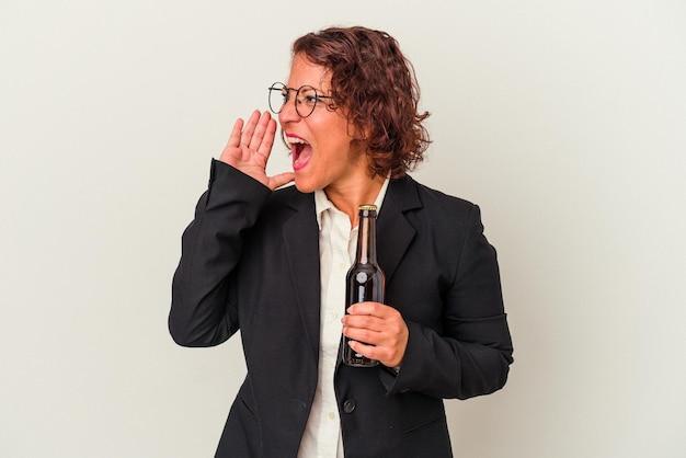 Femme d'affaires latine d'âge moyen tenant une bière isolée sur fond blanc criant et tenant la paume près de la bouche ouverte.