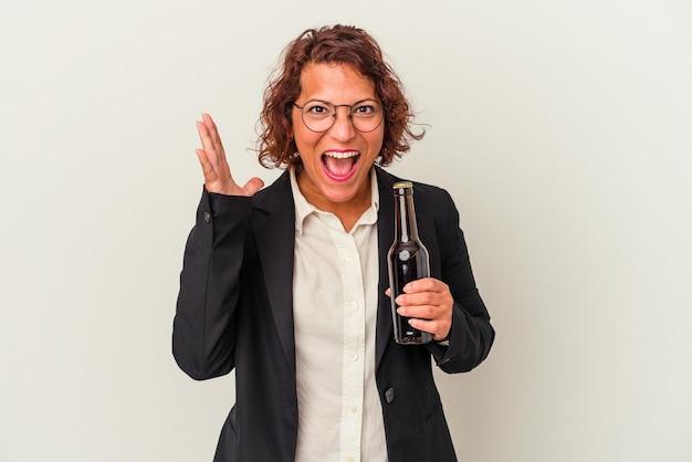 Femme d'affaires latine d'âge moyen tenant une bière isolée sur fond blanc recevant une agréable surprise, excitée et levant les mains.