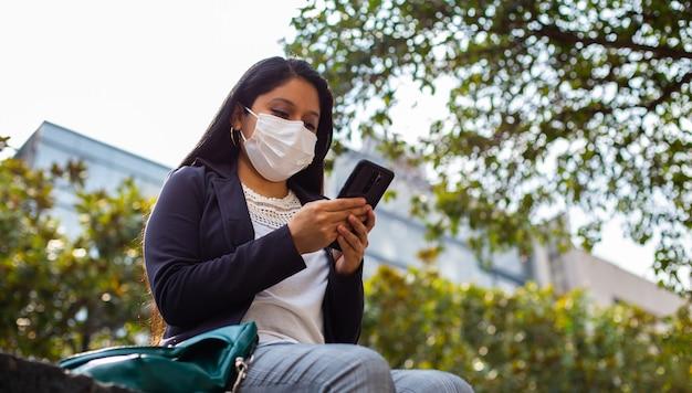 Femme d'affaires latine portant un masque facial pour des raisons de protection pendant la pandémie de covid