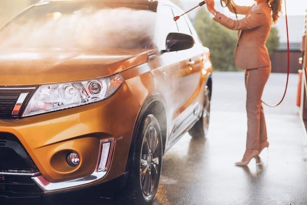 Femme d'affaires laver la voiture à la station de lavage de voiture à l'aide d'une machine à eau haute pression.