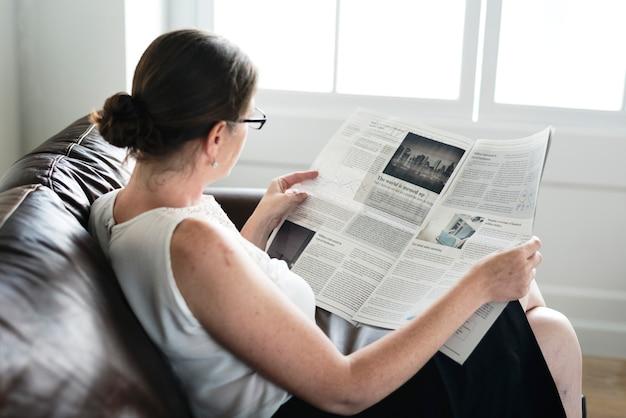 Femme affaires, lecture journal, sur, a, divan