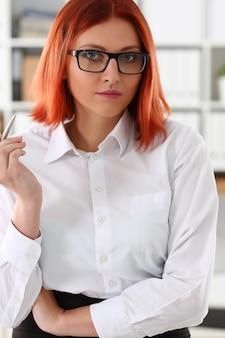 Femme d'affaires sur le lieu de travail dans le portrait de bureau dans un simple costume sourit
