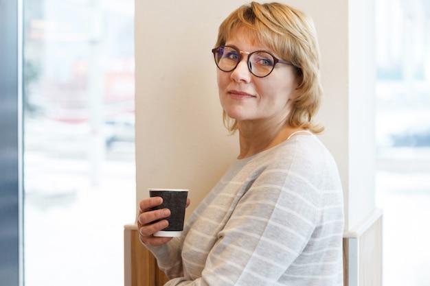 Femme d'affaires sur le lieu de travail à la fenêtre du bureau. une femme d'âge moyen tient un verre de café dans un café. elle sourit.