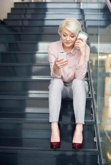 Femme d'affaires lisant un message texte dans les escaliers