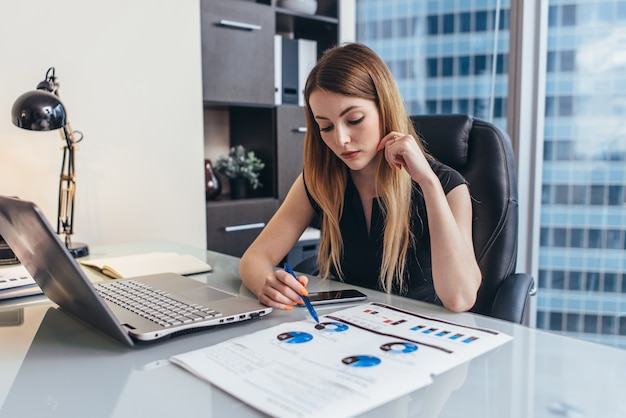 Une femme d'affaires lit un rapport financier analysant les statistiques pointant sur un camembert travaillant à son bureau.