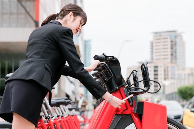 Femme d'affaires louant un vélo électrique partagé sur la rue de la ville sur le chemin du travail