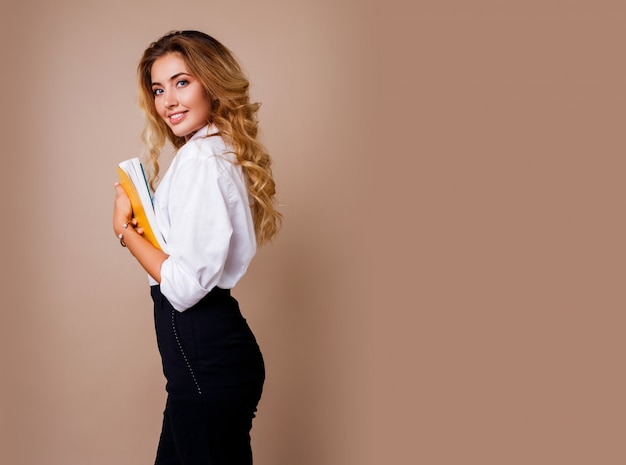 Femme d'affaires à lunettes élégantes debout sur un mur beige. cheveux ondulés blonds. chemisier blanc et pantalon noir.