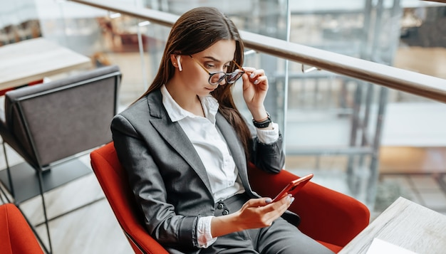 Une femme d'affaires à lunettes sur le lieu de travail utilise le téléphone et s'assoit à la table. gestionnaire au bureau.