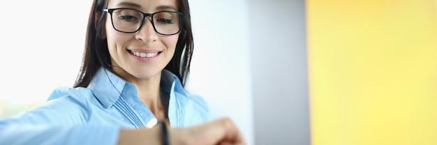 Une femme d'affaires avec des lunettes sourit et regarde sa montre