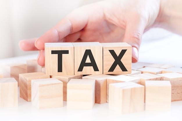 Femme d'affaires main changer le bloc de cube en bois avec mot taxe. concepts financiers, de gestion, commerciaux et économiques