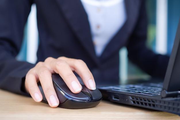 Femme d'affaires avec la main de doigt à l'aide de la souris ordinateur portable sur table en bois.