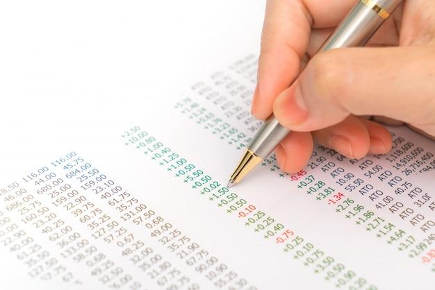 Femme d'affaires la main avec des graphiques financiers et un ordinateur portable sur le ta