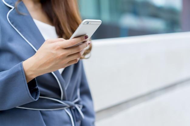 Femme d'affaires main tenant un smartphone pour vérifier le travail