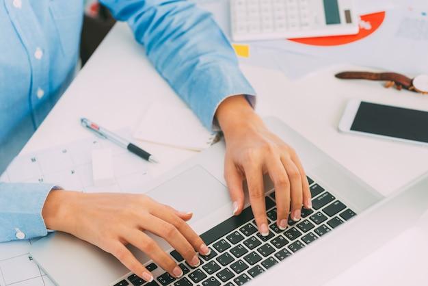 Femme d'affaires mains tapant clavier d'ordinateur portable sur le bureau avec espace de travail