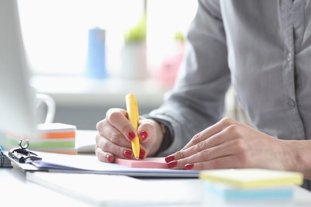 Femme d'affaires avec manucure rouge écrit avec un stylo sur des autocollants en papier libre