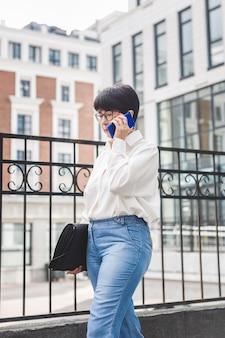 Femme affaires, marche, et, utilisation, téléphone portable