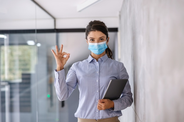 Femme d'affaires avec masque facial debout en entreprise avec tablette pendant le coronavirus et montrant un signe correct.